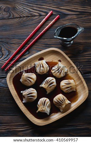 Bamboo tray with steamed chinese dim sums and soy sauce - stock photo
