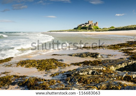 Bamburgh Castle with waves / Bamburgh Castle taken here from the north beach dates back to the 6/7th century - stock photo