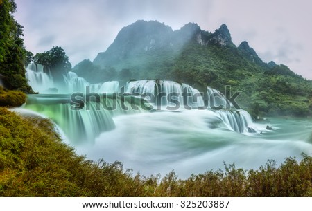 Ban Gioc Waterfall craggy limestone permissive side misty morning with foreground grass and tones of the lower cascade. It is considered the most beautiful waterfalls Asia. - stock photo