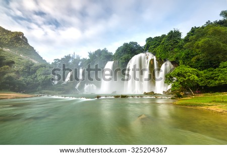 Ban Gioc Waterfall misty morning when strong winds made playing cloudy sky and the water smooth as silk carpets create ink strokes in picturesque - stock photo