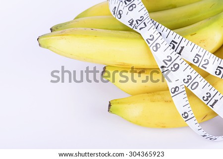 Banana and measurement tape on white background - stock photo