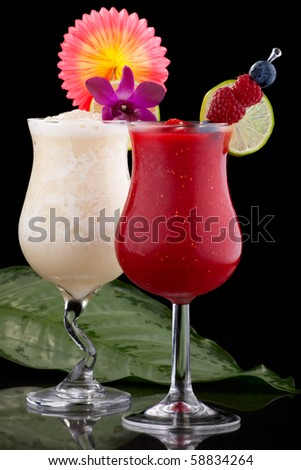 Banana and Raspberry Daiquiri cocktails. Rum, banana, raspberry, liqueur, lime juice garnished with lime and fresh raspberries over black background. Most popular cocktails series. - stock photo