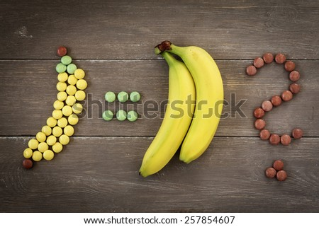 Banana and smarties, question mark - stock photo