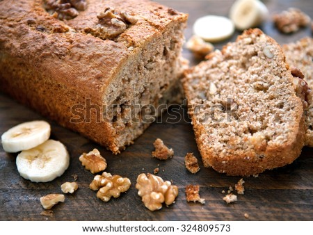 Banana and Walnut loaf cake cut open on wooden board close up - stock photo
