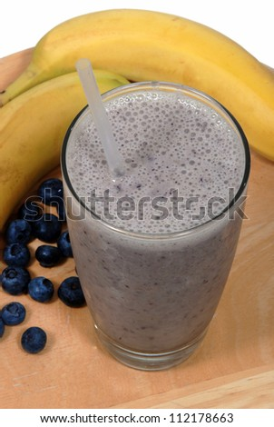 Banana, blueberry fruit smoothie in a glass near fresh, organic fruit - stock photo