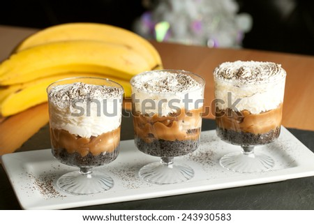Banana caramel parfait desserts with fresh whipped cream and chocolate cookie crumbles. - stock photo