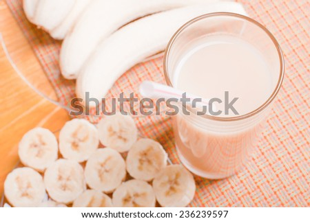banana juice in a glass on a yellow table beside peeled bananas - stock photo