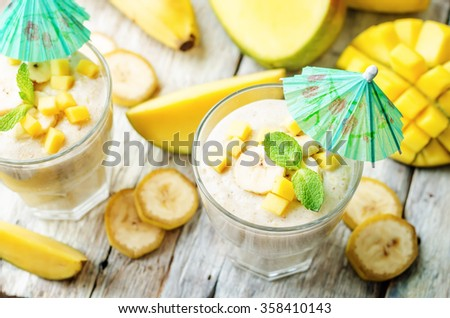 banana mango smoothie on a white wood background. toning. selective Focus - stock photo