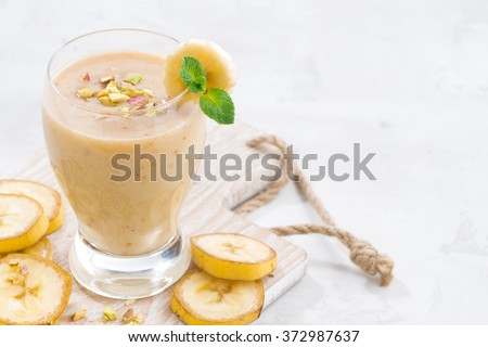 banana milkshake in a glass on white wooden board, closeup - stock photo