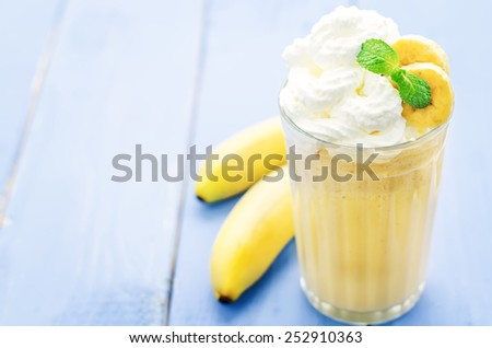 banana milkshake with whipped cream on a blue wood background. tinting. selective focus - stock photo
