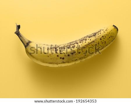 banana on a yellow background, tone on tone - stock photo