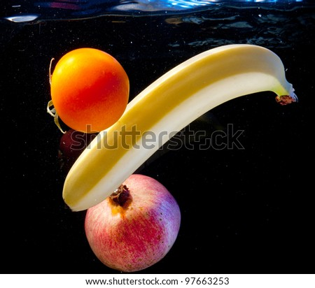 Banana, pomegranate and tomatoes in water for chornomi background - stock photo