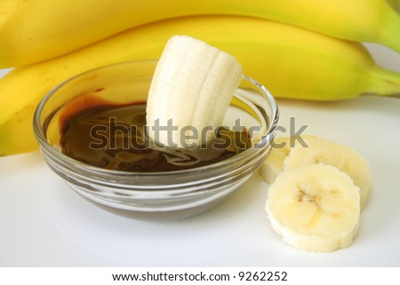 banana's and chocolate sauce on a white background. - stock photo