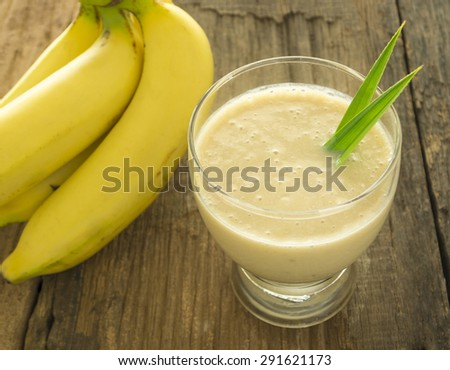 Banana smoothie in a glass is placed on a wooden table. - stock photo