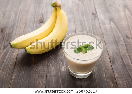 Banana smoothie on wooden table - stock photo