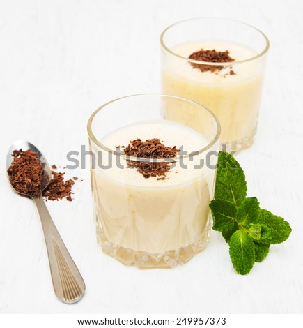 Banana smoothie with chocolate on a old white wooden background - stock photo