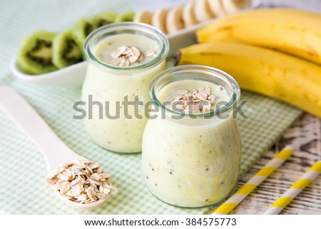 Banana smoothie with kiwi and oats on a light wooden table. Protein diet. Healthy food concept. - stock photo
