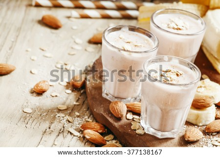 Banana smoothie with milk, oatmeal and almonds on the old wooden background, selective focus - stock photo
