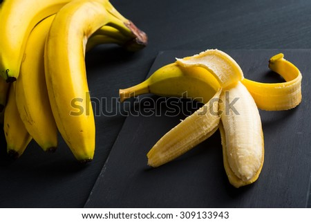 Bananas and peeled banana - stock photo