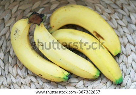 Bananas on wicker place mat - stock photo