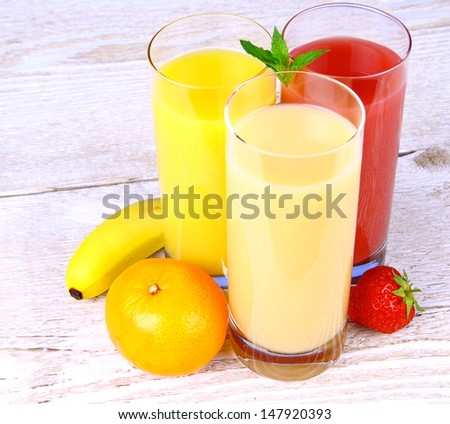 Bananas, strawberry and oranges juice in glass, top view - stock photo
