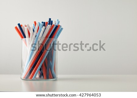 Banch of pastel vivid colored thick drinking straw in transparent glass pot isolated on white table - stock photo