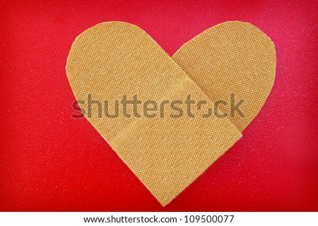 bandage in a heart shape, on red textured background - stock photo