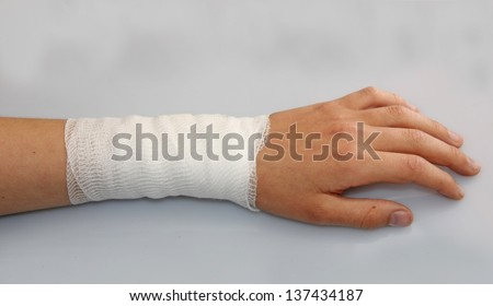 bandaged arm of a child because of a skin lesion - stock photo