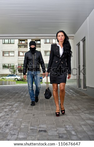 Bandit in mask following businesswoman. Robbery concept - stock photo