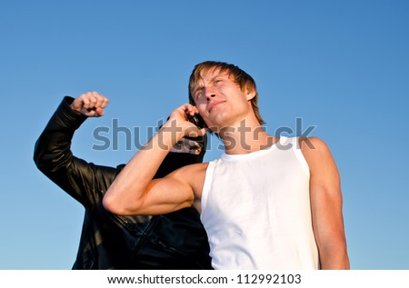 Bandit in mask trying to rob young man - stock photo