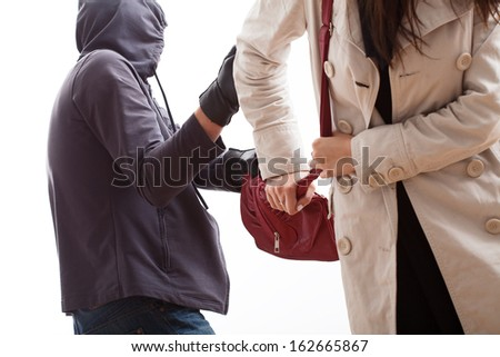 Bandit snatching a purse from a young woman - stock photo