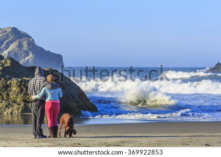 BANDON BEACH, OREGON COST, OREGON, USA - OCTOBER 22, 2015: People with dogs enjoy views of the ocean surf - stock photo