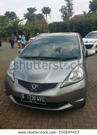 BANDUNG, WEST JAVA, INDONESIA- SEPTEMBER 15, 2014 : Honda Jazz parked in front of a popular tourist attraction location in Bandung, Indonesia. Honda Jazz also known as Honda Fit in Japan. - stock photo