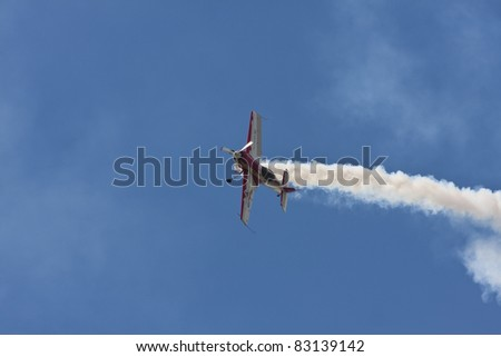 BANESTI, ROMANIA - AUGUST 6: Sukhoi Su-26 piloted by Jurgis Kairys from Lithuania performs during the 2011Banesti airshow on August 6, 2011 in Banesti, Romania. - stock photo