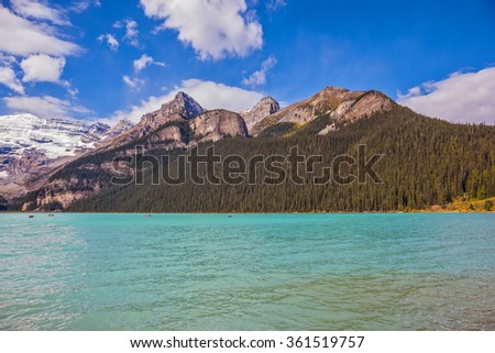 Banff National Park, Canada, Alberta. Magnificent Lake Louise with emerald green water surrounded by the Rocky Mountains, pine forests and glaciers - stock photo