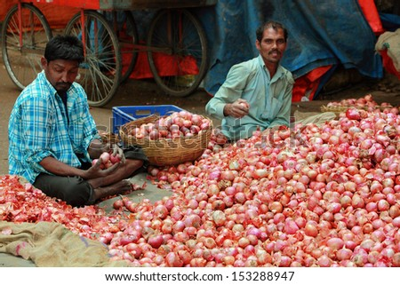 BANGALORE, INDIA - AUGUST 25: Unidentified venders selling onion on a city street on August 25, 2013 in Madiwala market, Bangalore, Karnataka, India. - stock photo