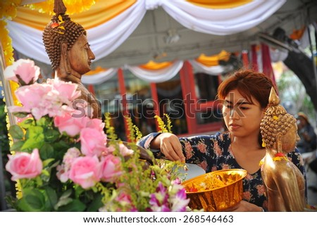 BANGKOK - APR 13: A temple goer pours water over a Buddha statue at a temple during a merit making ceremony to mark the traditional Thai New Year or Songkran on Apr 13, 2014 in Bangkok, Thailand. - stock photo