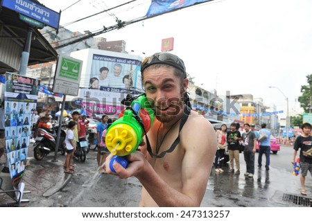 BANGKOK - APRIL 12: A reveller celebrates the Thai New Year near Khao San Road on April 12, 2013 in Bangkok, Thailand. The new year, or Songkran, is celebrated with street parties and water fights. - stock photo