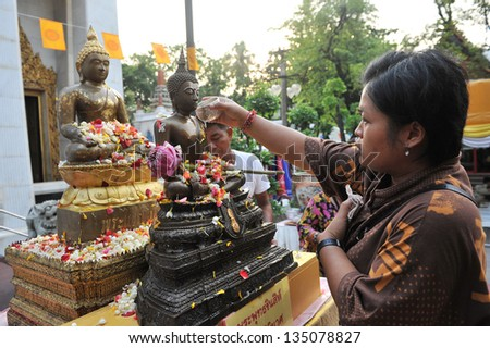 BANGKOK - APRIL 12: A woman pours water over a Buddha statue at a temple while taking part in traditional celebration of the Thai New Year, or Songkran, on April 12, 2013 in Bangkok, Thailand. - stock photo