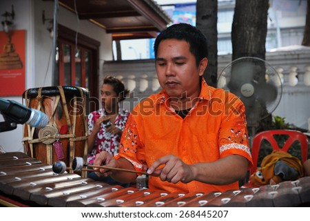 BANGKOK - APRIL 12: An unidentified musician plays a ranat at a Buddhist temple during activities welcoming in the Thai New Year, or Songkran, on April 12, 2013 in Bangkok, Thailand. - stock photo