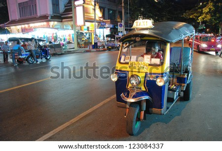 BANGKOK - AUG 10: A three wheeled tuk tuk taxi on a street in the Thai capital on August 10, 2009 in Bangkok, Thailand. Tuk tuks are commonly used in transporting people and goods around the capital - stock photo