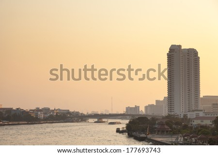 Bangkok city and river in evening. Has high buildings and bridges across the river in the evening. - stock photo