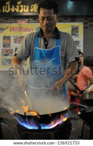 BANGKOK - DEC 13: A chef cooks food at a street-side restaurant in Chinatown on Dec 13, 2012 in Bangkok, Thailand. There are 16,000 registered street vendors in Bangkok according to government stats. - stock photo