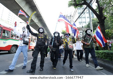 BANGKOK - DEC 9: Many Masked protesters walked for anti government corruption on December  09, 2013 in Bangkok, Thailand. The protesters required  Yingluck Shinawatra Prime Minister resign. - stock photo