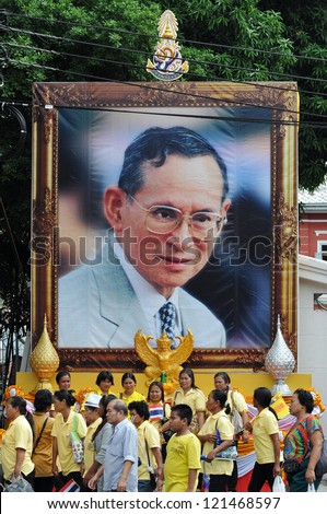 BANGKOK - DEC 5: Royalists walk past a large portrait of Thai King Bhumibol Adulyadej after attending celebrations of the King's 85th birthday on the Royal Plaza on Dec 5, 2012 in Bangkok, Thailand. - stock photo