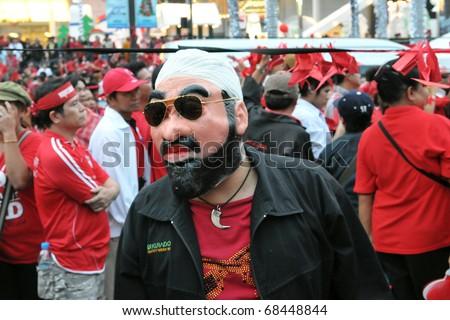 BANGKOK - DECEMBER 19: A Red Shirt wearing an Osama Bin Laden mask attends a 10,000 strong anti government rally at Rachaprasong junction on December 19, 2010 in Bangkok, Thailand. - stock photo