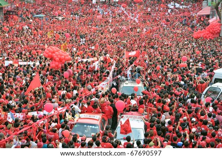BANGKOK - DECEMBER 19: An estimated 10,000 anti government Red Shirts defy an emergency decree to protest at Rachaprasong junction on December 19, 2010 in Bangkok, Thailand. - stock photo