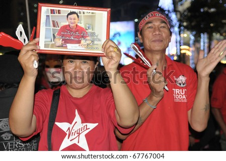 BANGKOK - DECEMBER 19: Red Shirts at a protest at Rachaprasong display an image of Thaksin Shinawatra, former PM of Thailand who was ousted in a 2006 coup on December 19, 2010 in Bangkok, Thailand. - stock photo