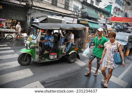 BANGKOK - FEB 4: A tuk tuk taxi ferries passengers along a street in Chinatown on Feb 4, 2012 in Bangkok, Thailand. Tuk tuks can be hired from as little as $1 per trip. - stock photo
