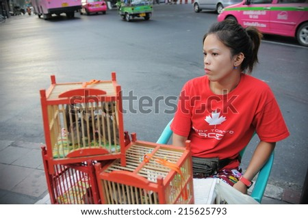 BANGKOK - FEB 11: An unidentified woman sells birds at a roadside stall outside the Erawan Shrine on May 24, 2013 in Bangkok, Thailand. Temple-goers believe sending birds free will bring good karma. - stock photo